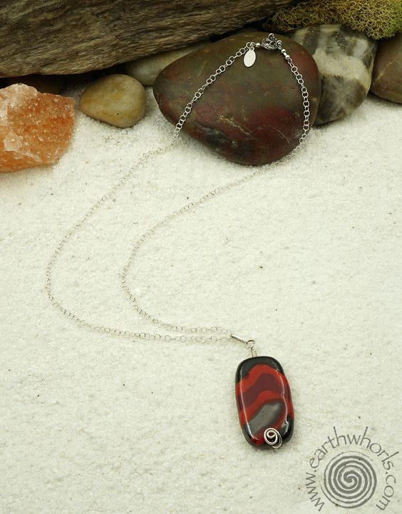 A single, red, black and gray, African clay bead of substantial size